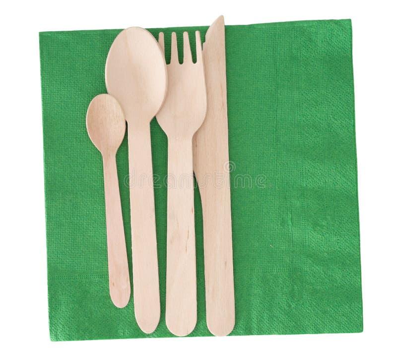 Cutelaria, forquilha da faca e colher de madeira, no guardanapo de papel verde, serviette, isolado no branco foto de stock royalty free