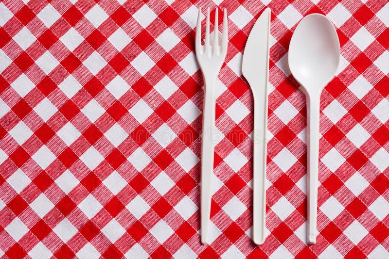 Cutelaria plástica em tablecloth checkered foto de stock