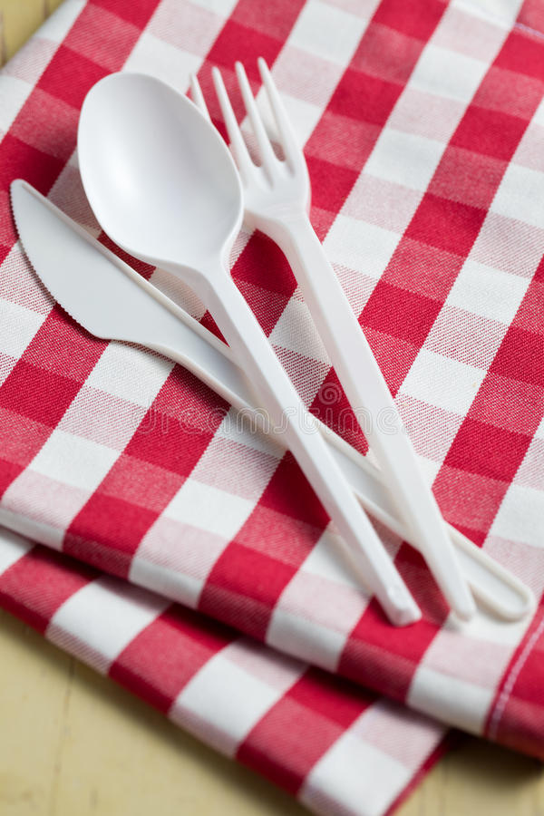 Cutelaria plástica em tablecloth checkered fotos de stock royalty free
