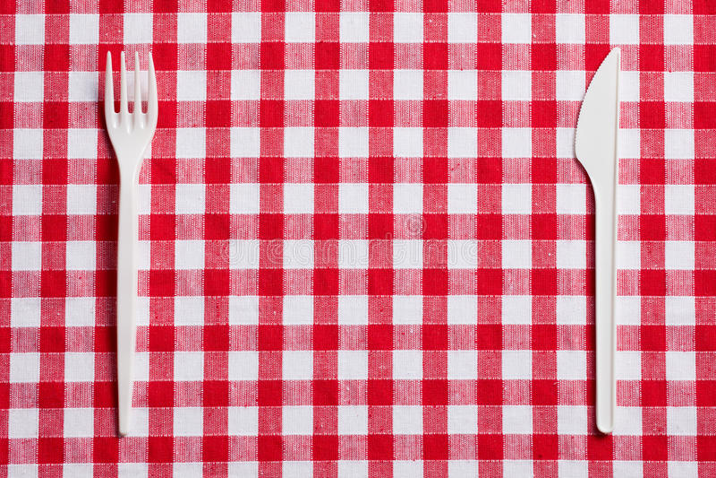 Cutelaria plástica em tablecloth checkered imagens de stock royalty free