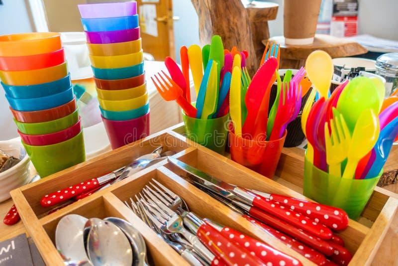 Cutelaria plástica segura da criança colorida, cutelaria adulta e copos empilhados foto de stock