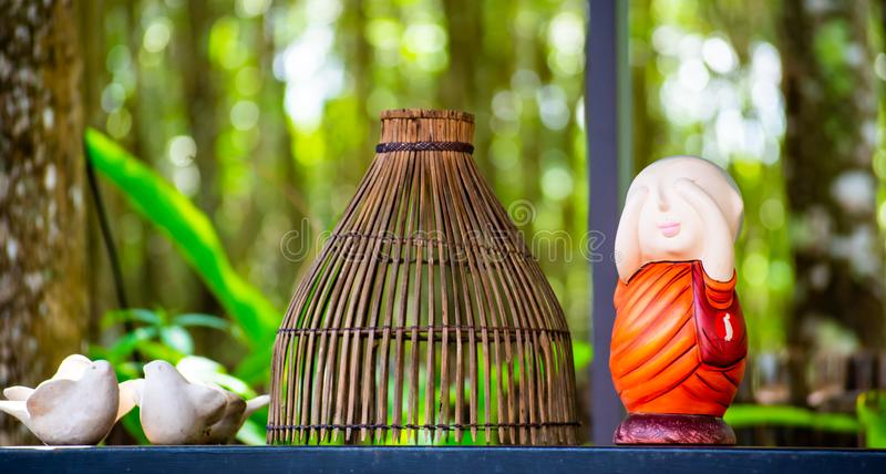 Cutes decoration , little monk doll and wooden baske in local cafe at Wat Rai Cheon Ta Wan , Chiangrai , Thailand. stock photos