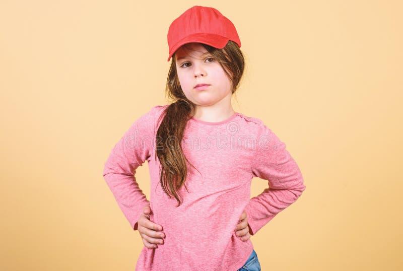 Cutie στην ΚΑΠ Μόδα παιδιών Αίσθημα βέβαιος με αυτήν την ΚΑΠ Χαριτωμένη ένδυση ΚΑΠ παιδιών κοριτσιών ή snapback μπεζ υπόβαθρο καπ στοκ εικόνα