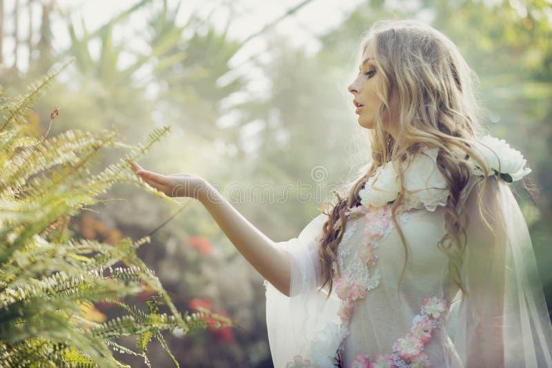 Cutie blond touchant les feuilles de la fougère photo stock