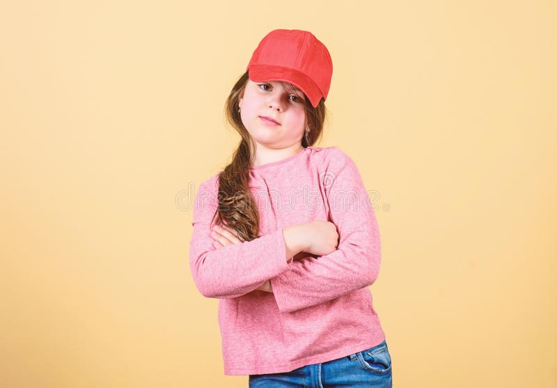 Cutie in cap. Modern fashion. Stylish accessory. Kids fashion. Feeling confident with this cap. Girl cute child wear cap. Or snapback hat beige background stock photography