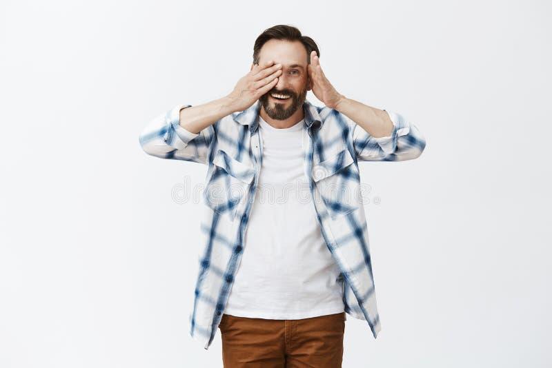Cutie do peekaboo Retrato do homem maduro considerável amigável e amável com barba, descolando a palma do olho e espreitando em foto de stock