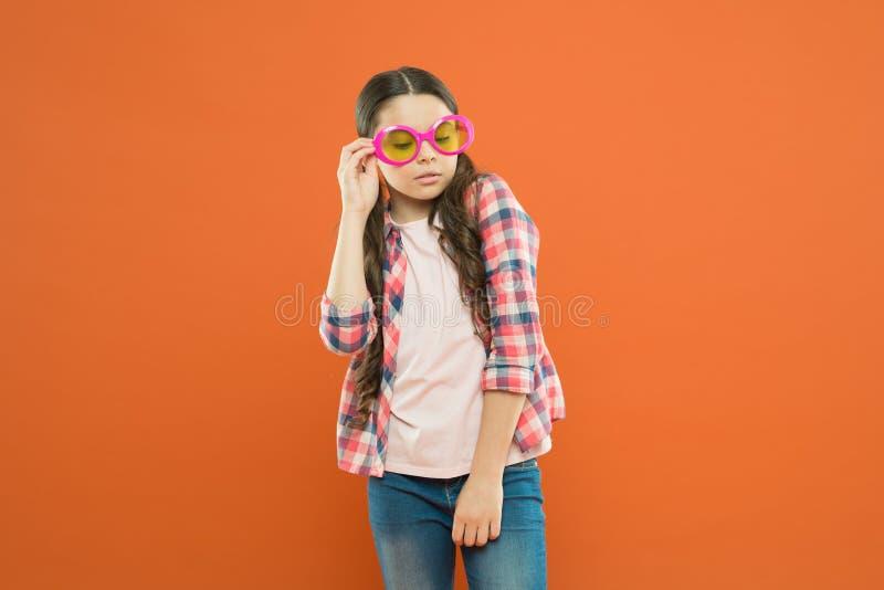 Cutie elegante Sendo esperto Pouco estudante esperta no fundo alaranjado Olhar esperto da criança através dos monóculos pequeno foto de stock royalty free