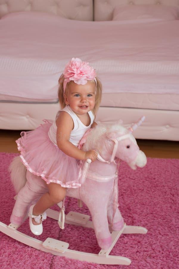 cutie little Liten blond häst för flickarittleksak Musikband för småbarnkläderhår Liten flicka med den långa frisyren hår arkivbilder