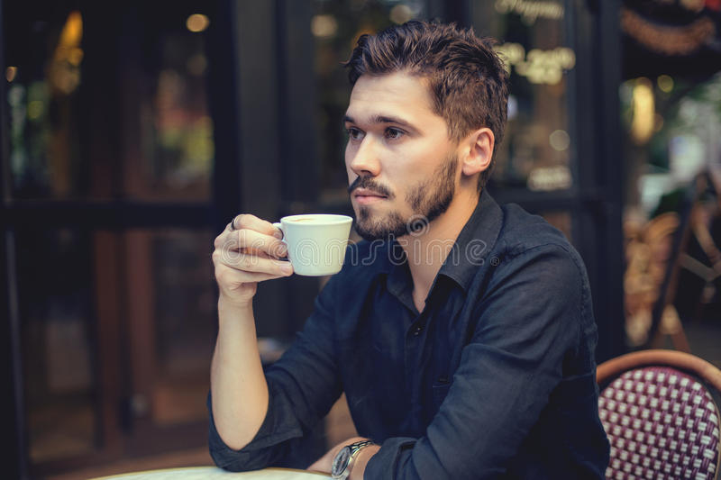 Cutie man with cup of coffee looking at mobile phone outdoors royalty free stock photos
