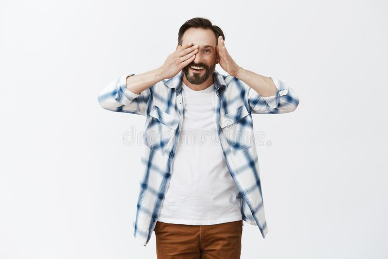 Cutie semi-transparent Portrait de mâle mûr beau amical et aimable avec la barbe, enlevant la paume de l'oeil et jetant un coup d photo stock
