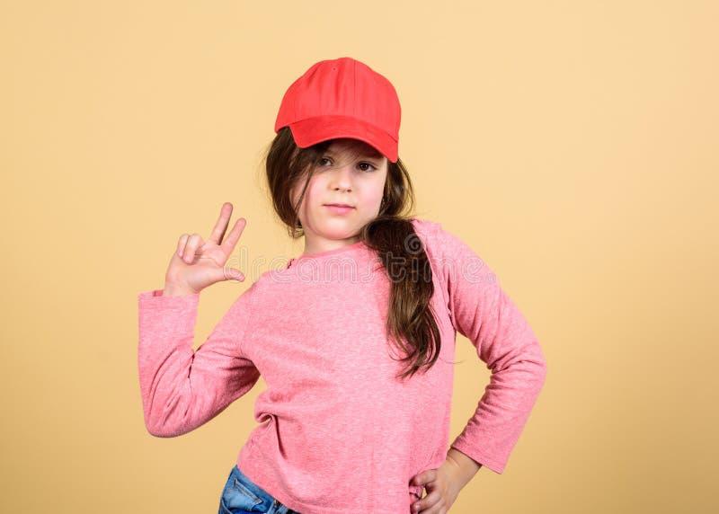 Cutie w nakr?tce Dziewczyny dziecka odzie?y ?liczna nakr?tka lub snapback kapeluszowy be?owy t?o Ma?a dziewczynka jest ubranym ja fotografia royalty free