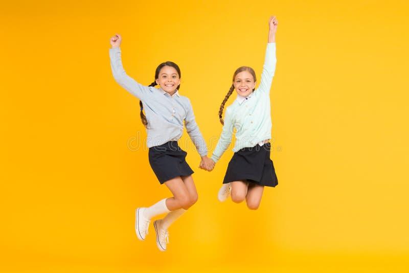 Cuties w w połowie powietrzu Aktywni dzieci skacze wysoko na żółtym tle Szczęśliwe dziewczyny cieszy się aktywnego styl życia szk zdjęcie royalty free