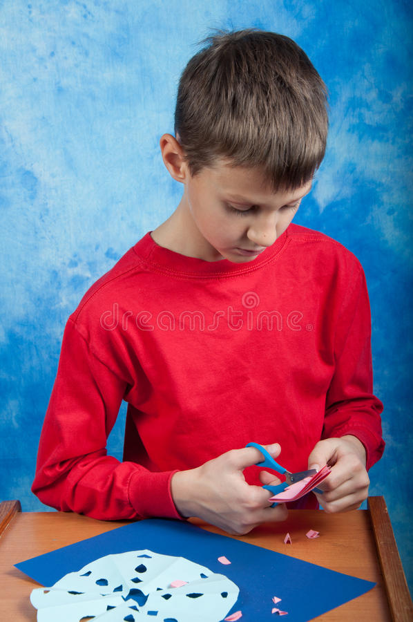 cuting与剪刀的男孩桃红色纸雪花 图库摄影