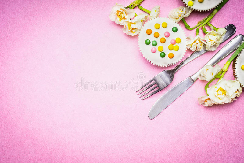 Cutlery with beautiful daffodils flowers and cake on pink background, top view, place for text. Easter food. And bake stock image
