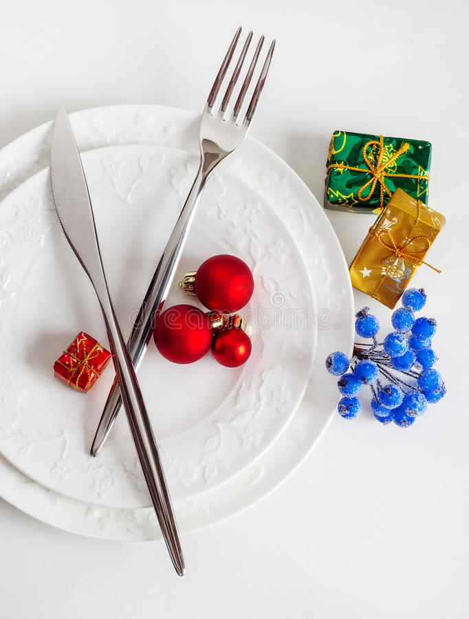 Cutlery for Christmas dinner. Porcelain plates and silverware with festive decorations for Christmas dinner in the white tones, new year, background, romance stock photography