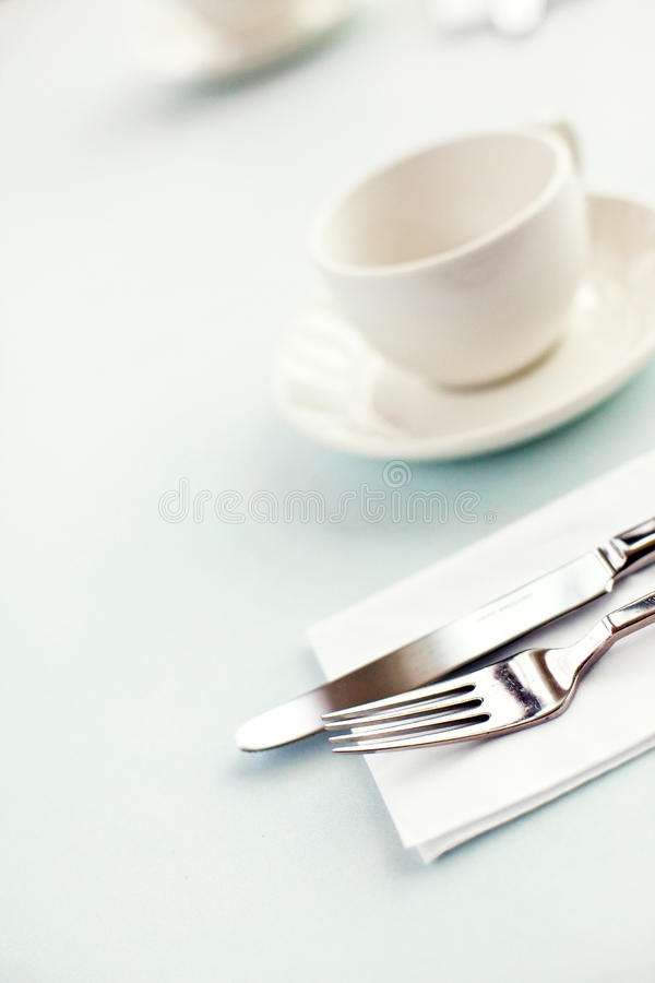 Cutlery and cup. Knife, fork and a cup on a table stock images