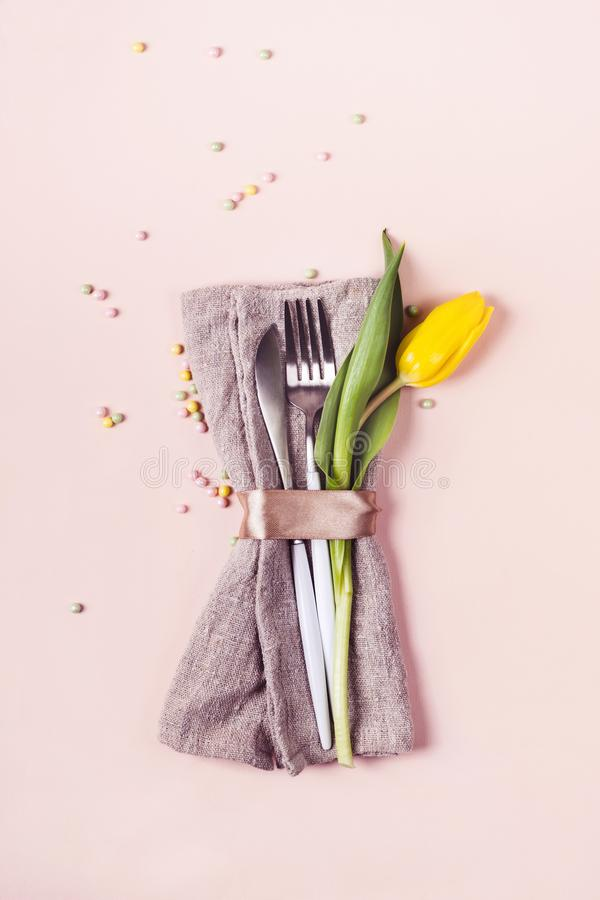 Cutlery dekoruje z pięknym żółtym tulipanem na pastelowych menchii tle Wiosny Easter stołu położenie zdjęcia royalty free