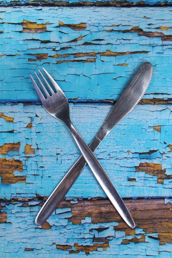 Cutlery - fork,knife. These are cutlery on blue wooden backdrop royalty free stock image