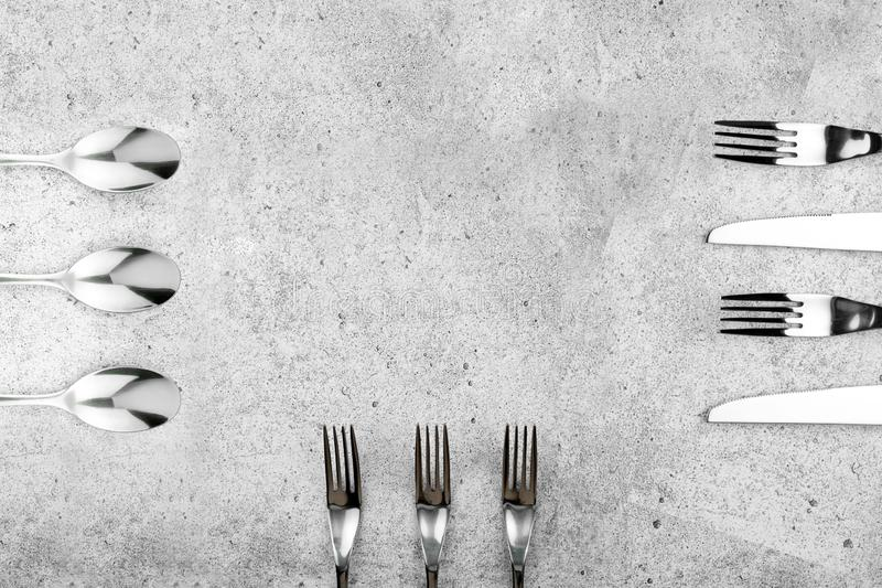 Cutlery. Forks and knives on a light concrete background. Place for an inscription. Flat lay, top view, copy space. stock images