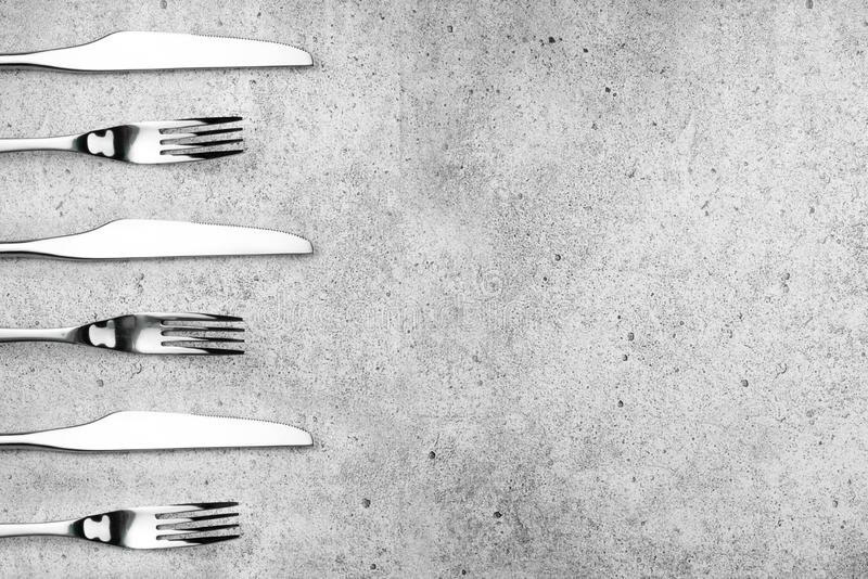 Cutlery. Forks and knives on a light concrete background. Place for an inscription. Flat lay, top view, copy space. royalty free stock images