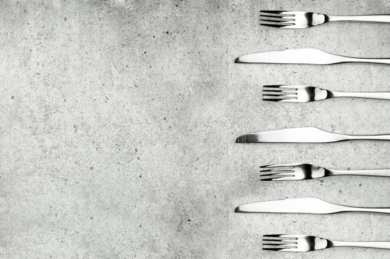 Cutlery. Forks and knives on a light concrete background. Place for an inscription. Flat lay, top view, copy space. royalty free stock photos