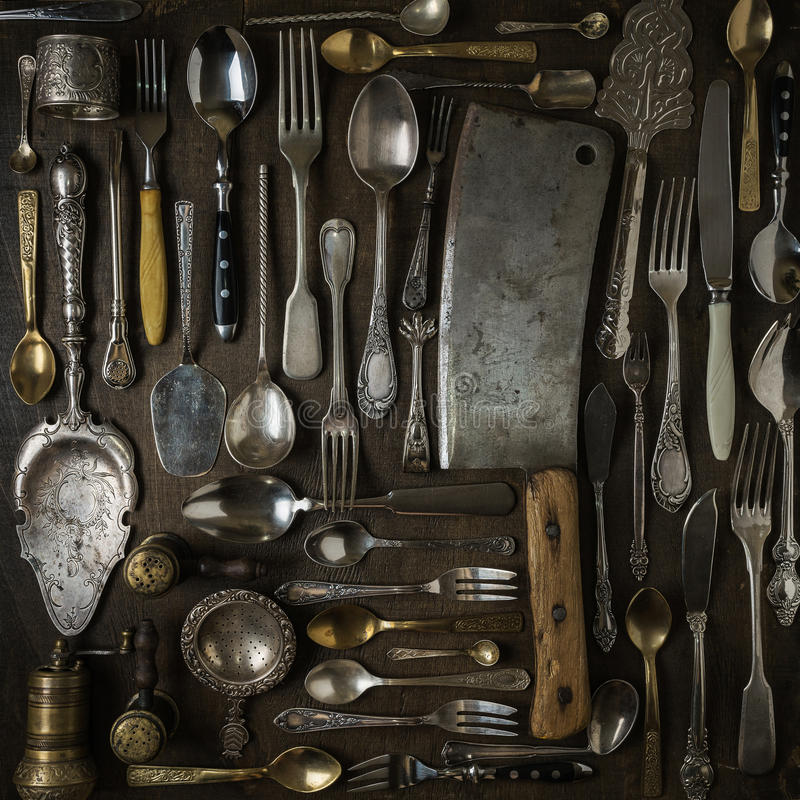 Cutlery, forks, spoons, and knives on dark wooden background stock photography