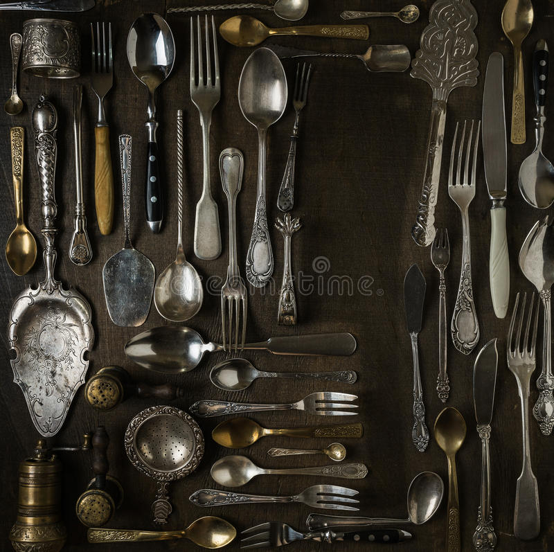 Cutlery, forks, spoons, and knives on dark wooden background royalty free stock photography