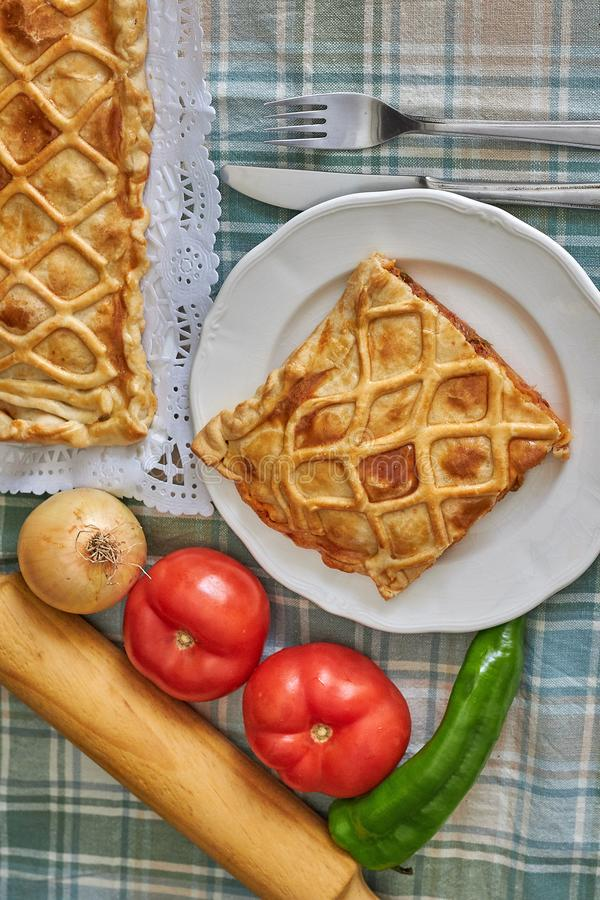 Galician tuna pie with onion, pepper and tomato. With cutlery and green checkered tablecloth royalty free stock photo