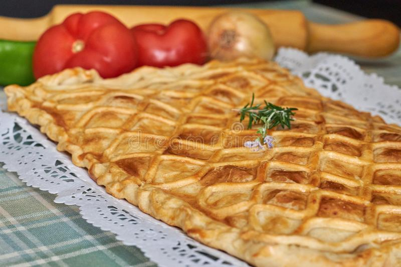 Galician tuna pie with onion, pepper and tomato. With cutlery and green checkered tablecloth royalty free stock images