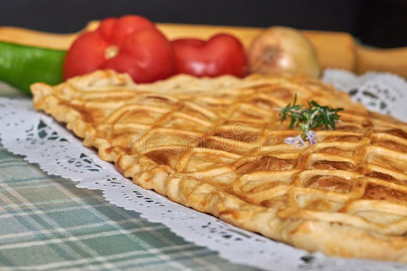 Galician tuna pie with onion, pepper and tomato. With cutlery and green checkered tablecloth stock photography