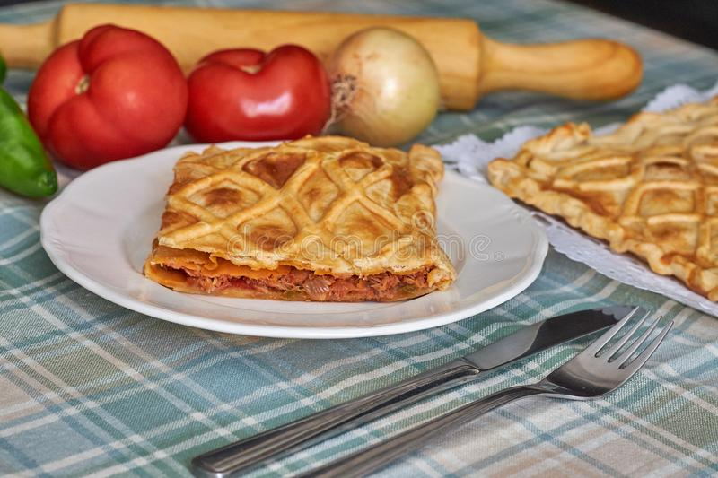 Galician tuna pie with onion, pepper and tomato. With cutlery and green checkered tablecloth stock images