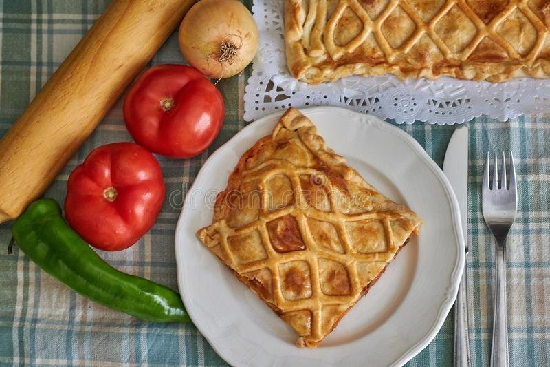 Galician tuna pie with onion, pepper and tomato. With cutlery and green checkered tablecloth royalty free stock photography