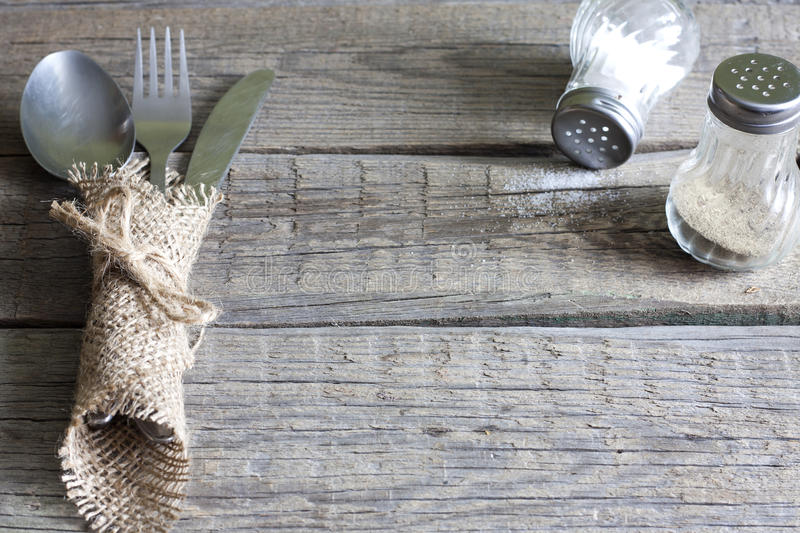 Cutlery kitchenware on old wooden boards background. Food concept stock photography