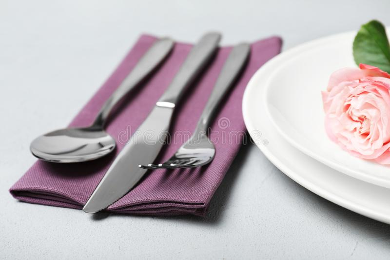 Cutlery and napkin on grey table, closeup stock photo