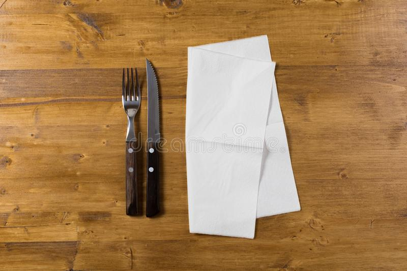 Cutlery and paper napkin on wooden background royalty free stock photo