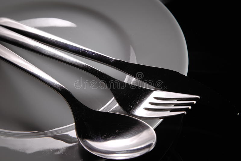 Cutlery on a plate. Simple view of cutlery on an empty plate stock image
