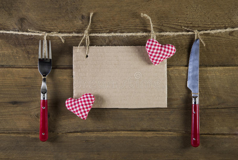 Cutlery in red color with empty advertising board and two red white checkered hearts on the background. Cutlery in red color: advertising board and two red stock photography