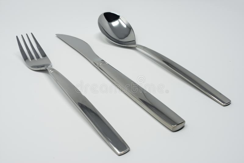Cutlery set, including silver stainless steel fork, spoon and knife. Cutlery set, including a silver stainless steel fork, spoon and knife. Isolated on a white stock photography
