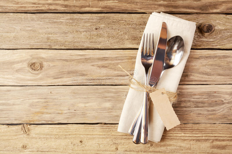 Cutlery Tied on Napkin with Tag on Wooden Table. Close up Spoon, Fork and Knife Tied on White Napkin with Empty Tag, on Wooden Table with Text Space royalty free stock photos