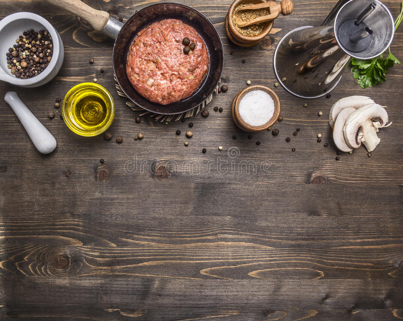 Cutlet of ground beef in a small frying pan, sliced mushrooms, pepper, herbs and salt border ,place text wooden rustic back. Cutlet of ground beef in a small royalty free stock photography