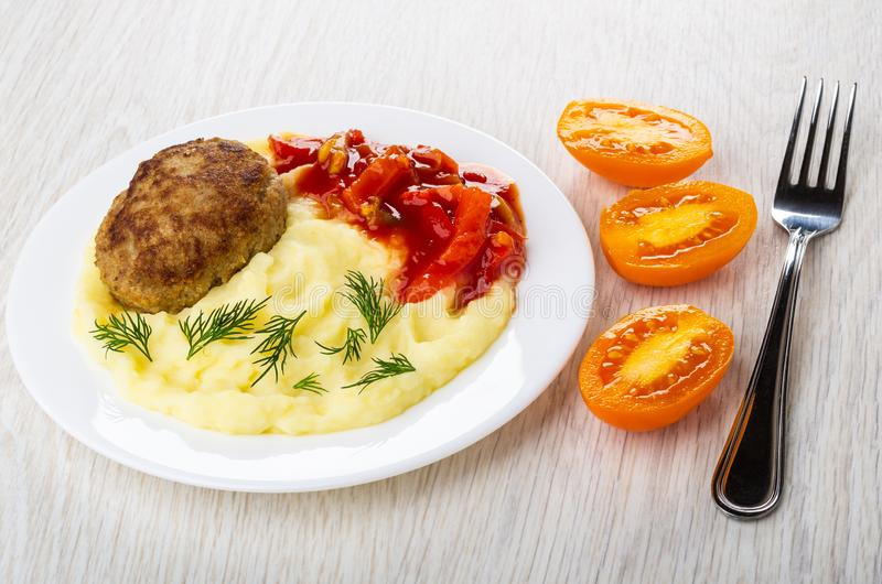 Cutlet with mashed potato, lecho in plate, tomatoes, fork on table. Fried cutlet with mashed potato, lecho in white plate, pieces of tomatoes, fork on wooden royalty free stock images