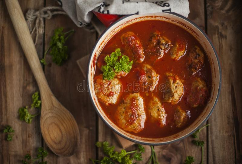 Cutlets κρέατος στη σάλτσα ντοματών, που ψήνεται σε ένα τηγανίζοντας τηγάνι Διακοσμημένος με το μαϊντανό σε ένα ξύλινο υπόβαθρο,  στοκ εικόνες