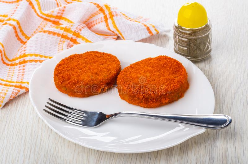 Cutlets in breading, fork in dish, pepper, napkin on table. Cutlets in breading, fork in white dish, pepper, checkered napkin on wooden table royalty free stock photos