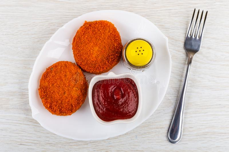 Cutlets in breading, pepper, ketchup in dish, fork on table. Top. Cutlets in breading, pepper, ketchup in white dish, fork on wooden table. Top view stock photos