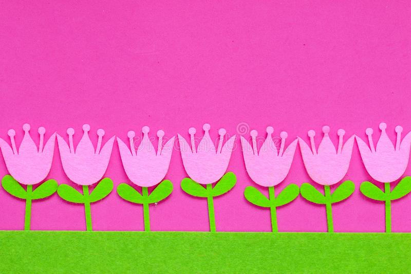 Brightly colored felt tulip flowers on a plain background stock image