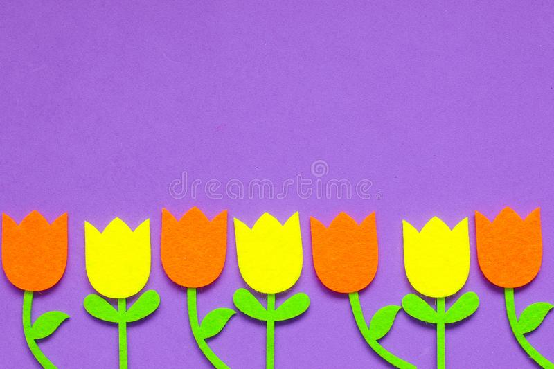 Brightly colored felt tulip flowers on a plain background royalty free stock image