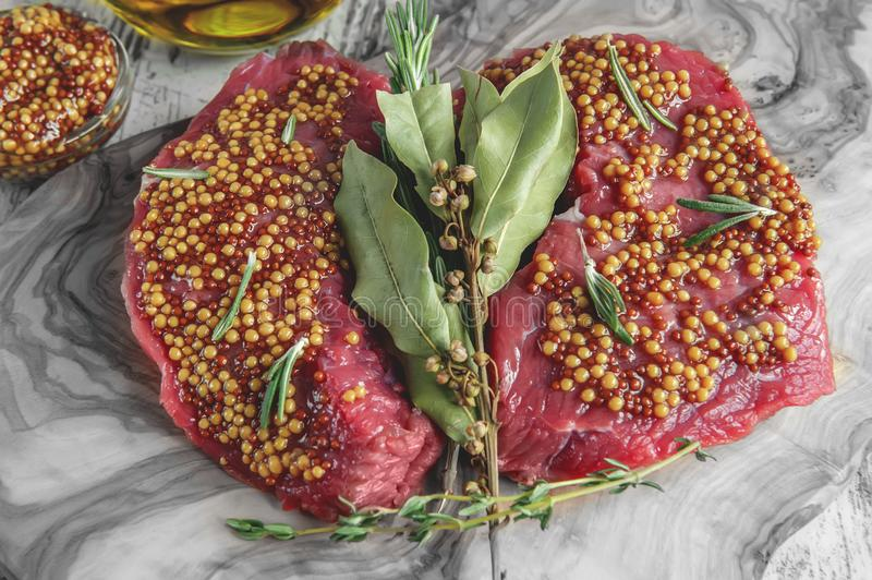Cuts of beef for grilling on a cutting Board olive wood with pickled Dijon mustard, rosemary and herbs de Provence in a rustic sty stock photography