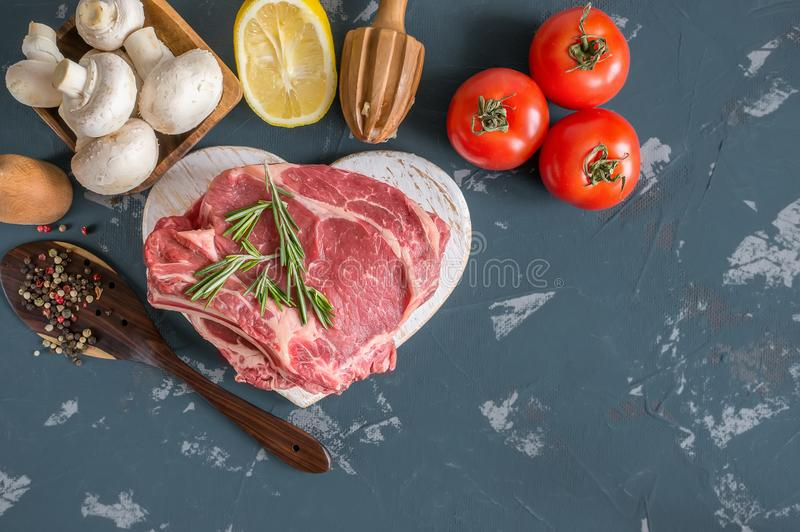 Cuts of beef for grilling on a wooden cutting Board with the Bay leaf, rosemary, olive oil and Provencal herbs for the marinade in. A rustic style. A horizontal royalty free stock photos