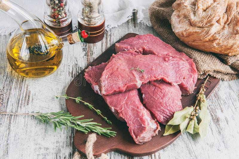 Cuts of beef for grilling on a wooden cutting Board with the Bay leaf, rosemary, olive oil and Provencal herbs for the. Marinade in a rustic style. A horizontal royalty free stock photography