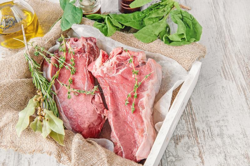 Cuts of beef for grilling on a wooden cutting Board with spinach, rosemary and Provencal herbs for the marinade in a. Rustic style. The horizontal frame stock images